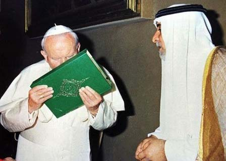 Pope John Paul kissing a copy of the Holy Quran